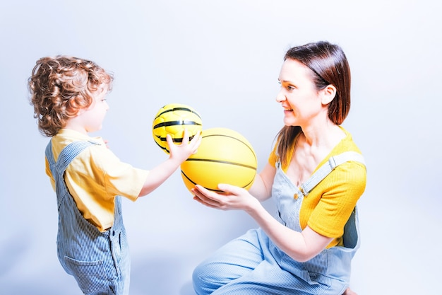 Genitore single giovane madre adulta che gioca con suo figlio con una palla da basket e da calcio. concetto gioca con i bambini. madre single. sport a scuola
