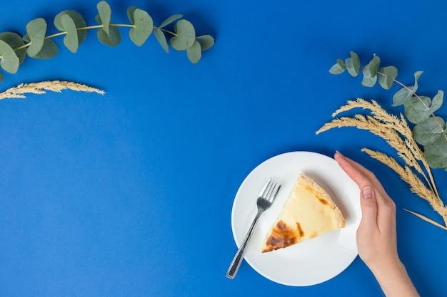 Pezzo singolo di cheesecake su un piatto bianco su sfondo blu. menu o concetto di cibo. banner rustico piatto, vista dall'alto, copia spazio.