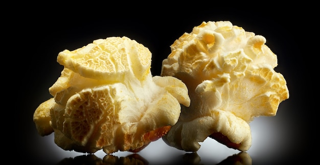 Popcorn schioccato singolo su uno sfondo nero con la riflessione. primo piano o macro.