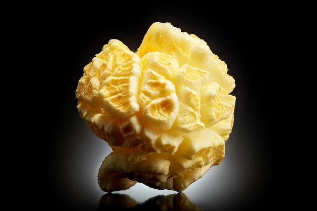 Popcorn schioccato singolo su uno sfondo nero con la riflessione. primo piano o macro. Foto Premium