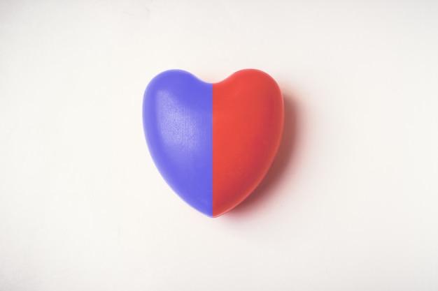 Singolo pallone di gommapiuma rosso-blu a forma di cuore. idea per la giornata mondiale della salute del cuore.