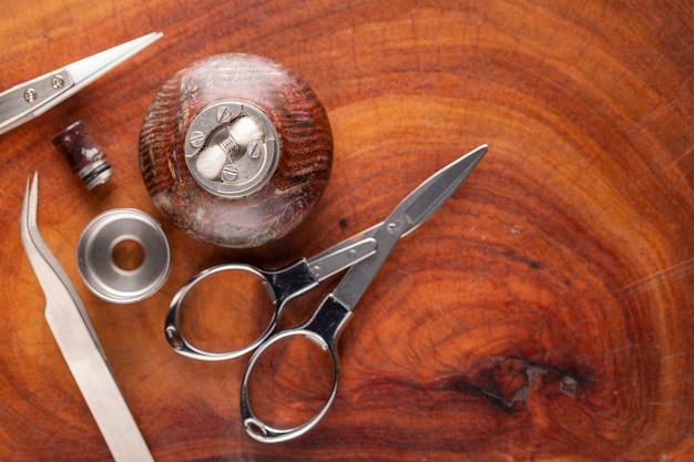 Bobina a spazio singolo con cotone in atomizzatore gocciolante ricostruibile su supporto in legno stabilizzato con forbici e pinzette su sfondo texture legno naturale, attrezzatura per vaporizzatore in processo di assorbimento, messa a fuoco selettiva