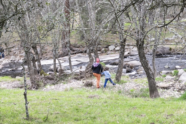 Una famiglia monoparentale passeggia nella natura evitando la folla di persone