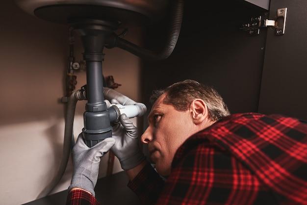 Primo piano di riparazione del sifone del lavandino del tuttofare anziano che ripara il lavabo