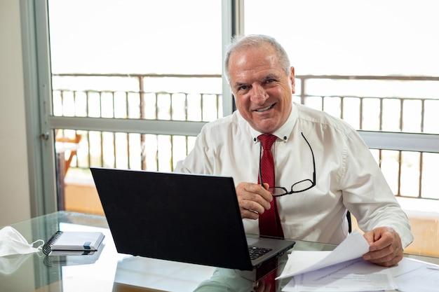 Signore che scrive sul notebook, lavora al sistema home office. mister lavora a casa indossando camicia e cravatta con la sua maschera appoggiata accanto.