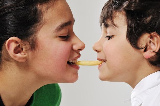Sorella e fratello che mangiano le patate fritte