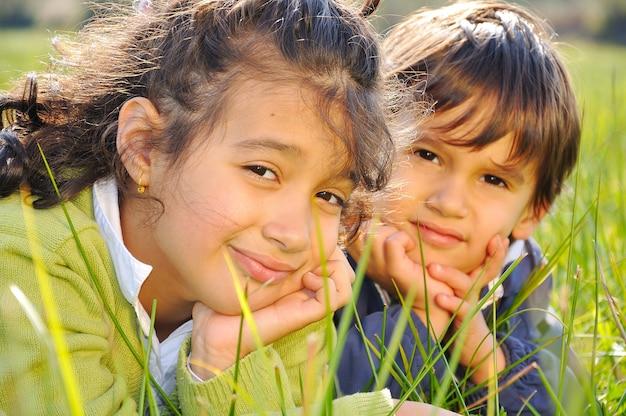 Sorella e fratello sul prato verde
