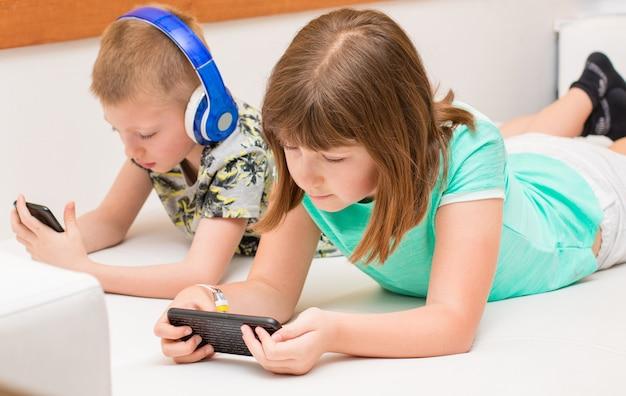 Sorella e fratello che giocano a giochi online su smartphone a casa