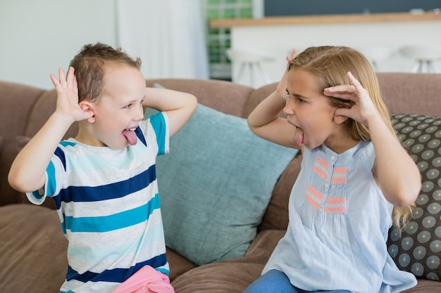 Sorella e fratello sporgono la lingua l'un l'altro sul divano del soggiorno
