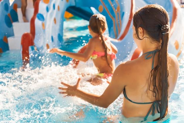 La sorella sorprende la sorella minore che scivola giù per lo scivolo direttamente in piscina