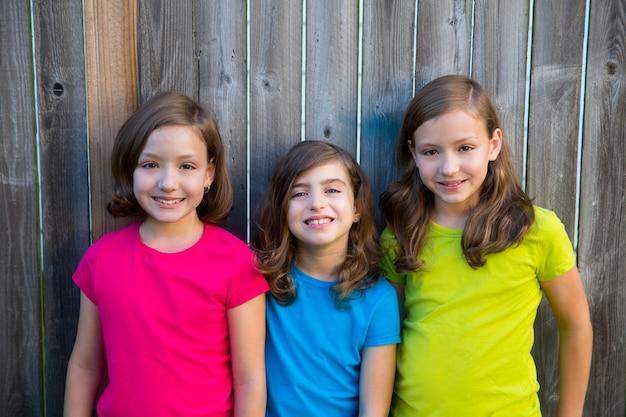 Sorella e amici ragazzino ritratto di ragazze sorridente sul recinto grigio