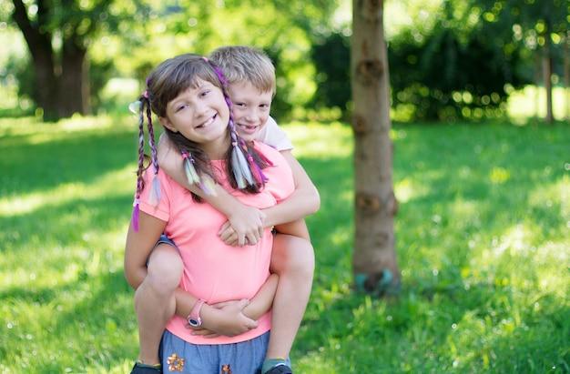 Una sorella porta in spalla il fratellino al parco