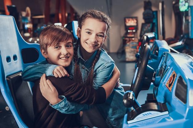 La sorella fa il tifo. il ragazzo sta guidando un'auto blu in sala giochi.