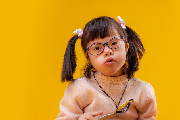 Sorelle che mangiano latte. curiosa piccola ragazza funky che tiene grande cucchiaio di metallo mentre si mangia