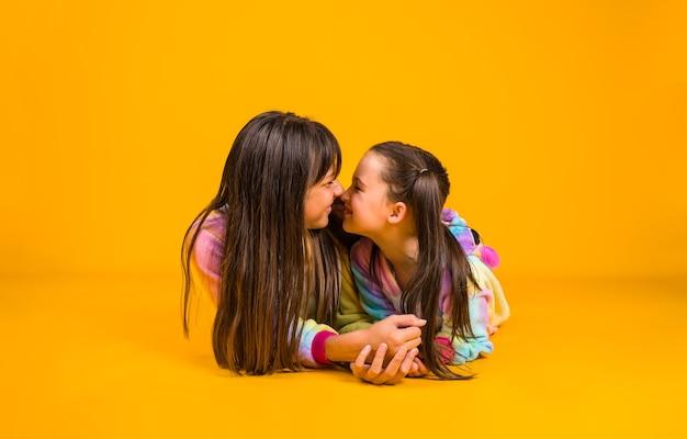 Le sorelle in pigiama di peluche giacciono e si abbracciano su uno sfondo giallo con una copia dello spazio