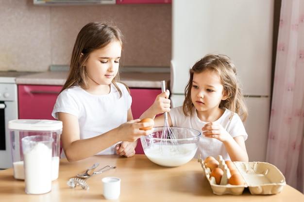 Le sorelle preparano la colazione, i pasticcini, mescolano la farina, il latte, le uova, i pancake in una ciotola, i bambini aiutano la madre, la famiglia colazione, cucina