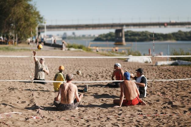 I giocatori di pallavolo amputati sedersi disabili giocano in spiaggia