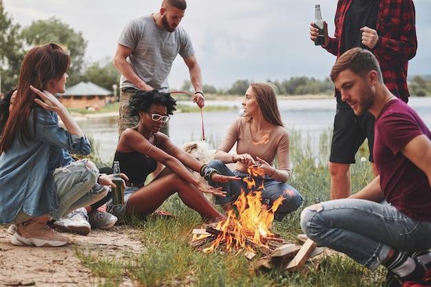 Si siede vicino al fuoco. un gruppo di persone fa un picnic sulla spiaggia. gli amici si divertono durante il fine settimana.