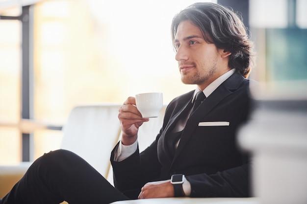 Si siede sul divano con una tazza di bevanda. ritratto di bel giovane uomo d'affari in abito nero e cravatta.