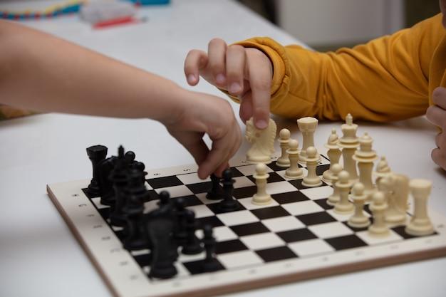 Si siede a un tavolo e gioca a scacchi. il ragazzo si concentra sul gioco e pensa a dove fare la sua prossima mossa. sviluppo precoce, giochi educativi per la casa per bambini