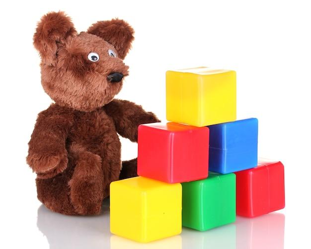 Orso seduto giocattolo e cubi colorati isolati su bianco