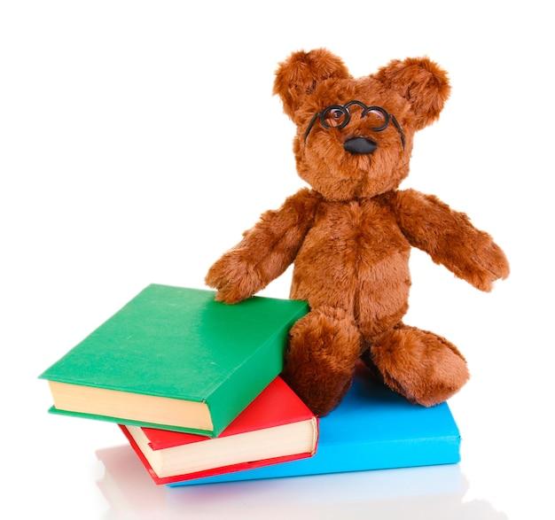 Orso seduto giocattolo con libri isolato su bianco