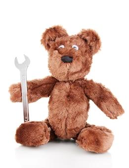 Orso seduto giocattolo con chiave inglese isolato su bianco