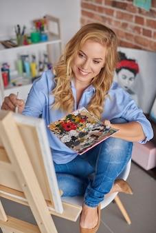 Sedersi su una sedia e dipingere sul cavalletto
