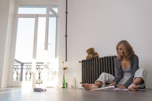 Seduta sul pavimento, una donna costruisce aeroplani con fogli di carta su cui sono stampati degli appunti