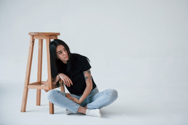 Sedendo sul pavimento. la giovane teenager bruna femminile ha un servizio fotografico in studio durante il giorno