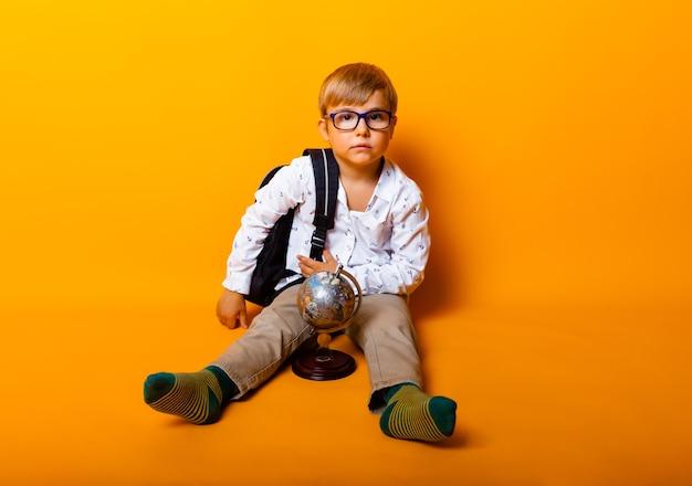 Lo scolaro seduto con gli occhiali tiene il globo del mondo isolato su sfondo giallo