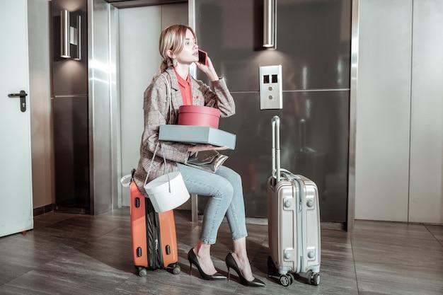 Seduto sulla valigia. moglie bionda impegnata seduta sulla valigia e chiama il marito che lo aspetta