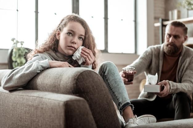 Seduto con la schiena. adolescente depresso dai capelli scuri seduto con le spalle al terapista e piangendo