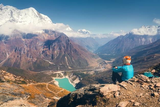 Donna seduta contro il bellissimo lago e le montagne