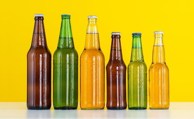 Sei bottiglie di birra su una parete gialla