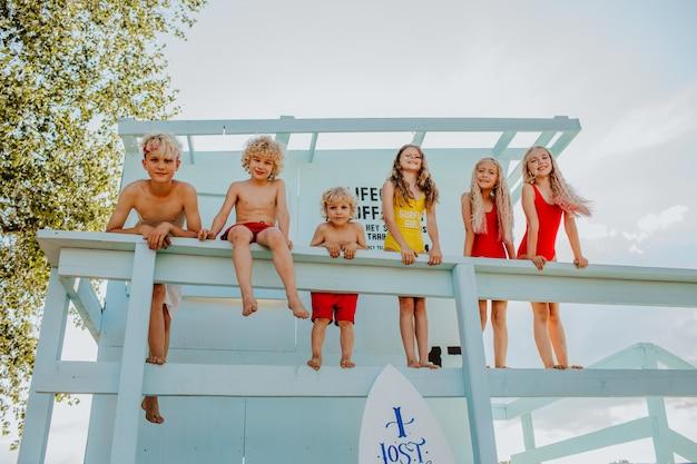 Sei simpatici bambini biondi in abiti estivi in posa sulla spiaggia di sabbia con torretta blu del bagnino e tavola da surf. felicità.