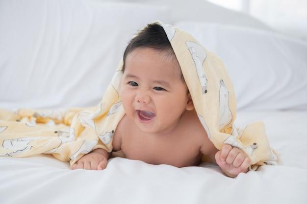 Bambino di sei mesi che indossa un asciugamano dopo il bagno