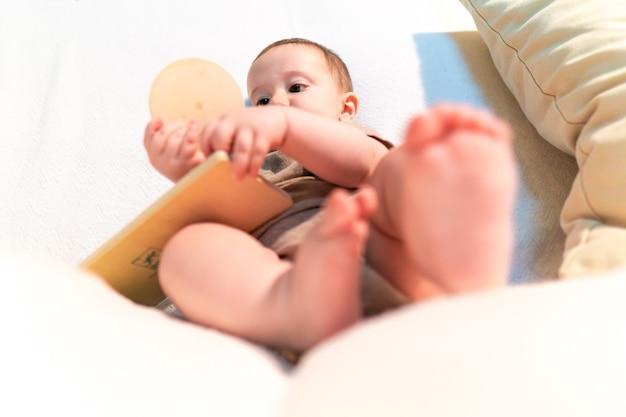 Bambino di sei mesi che gioca con un giocattolo di legno montessori