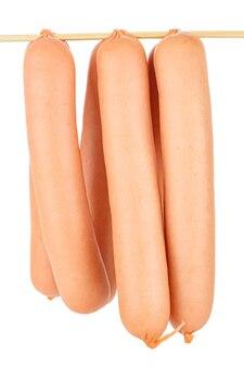 Sei salsicce crude in guscio naturale appeso al bastone di bambù isolato su bianco