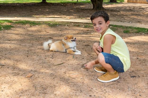 Bambino di sei anni accovacciato e accanto a un cane di razza lulu pomerania