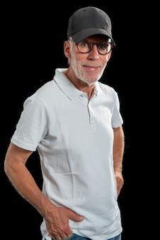 Uomo di sessant'anni che indossa un berretto da baseball su sfondo nero