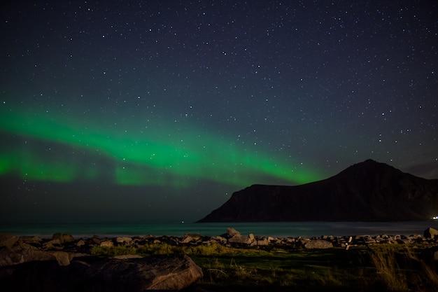 Paesaggio notturno della spiaggia di skagsanden con aurora boreale, alle lofoten, norvegia