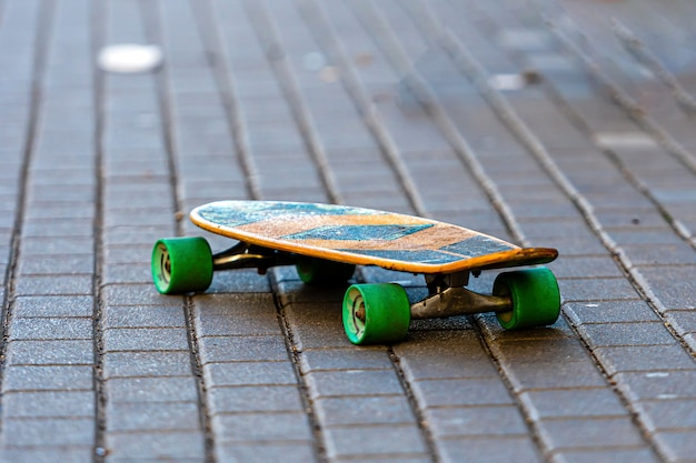 Skateboard con ruote verdi su un marciapiede pavimentato, close-up