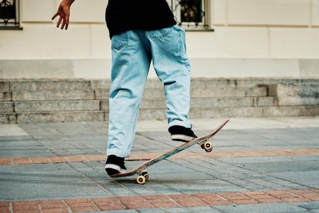 Skateboarder giro sullo skateboard alla strada della città da vicino
