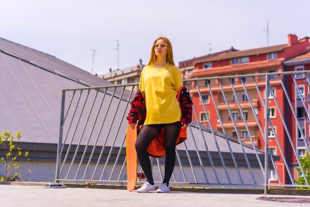 Skateboarder donna con una camicia gialla, camicia a quadri rossa e occhiali da sole, in posa con lo skateboard