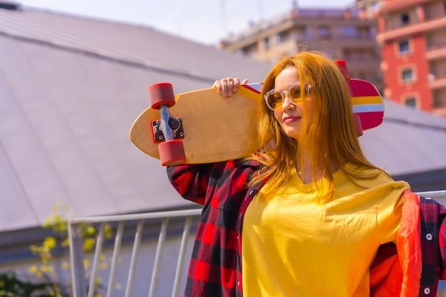 Skateboarder donna in una camicia gialla, camicia a quadri rossa e occhiali da sole, in posa con lo skateboard rivolto a sinistra