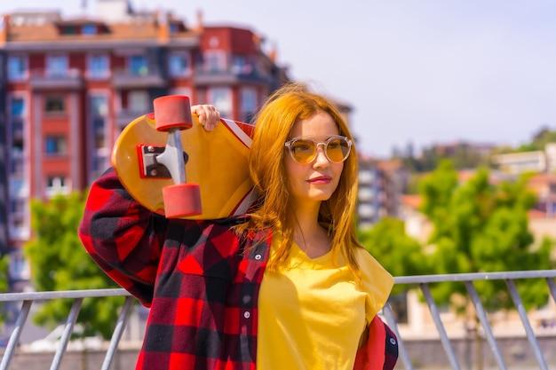 Skateboarder donna in camicia gialla, camicia a quadri rossa e occhiali da sole, in posa con lo skateboard che guarda a destra