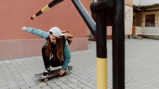 Ragazza pattinatrice nell'urbano in sella allo skateboard