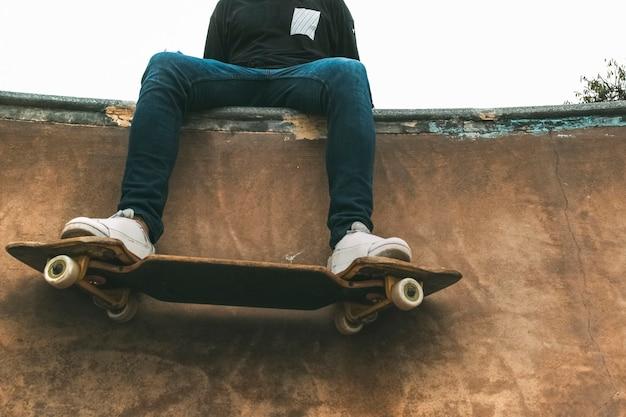 Pattinatore su uno snakeboard seduto su una rampa di viaggio in città concetto di stile di vita moderno copia spazio