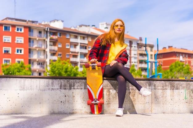 Skater donna in una t-shirt gialla, camicia a quadri rossa e occhiali da sole, seduta con lo skateboard su una panchina in città sorridente guardando la fotocamera